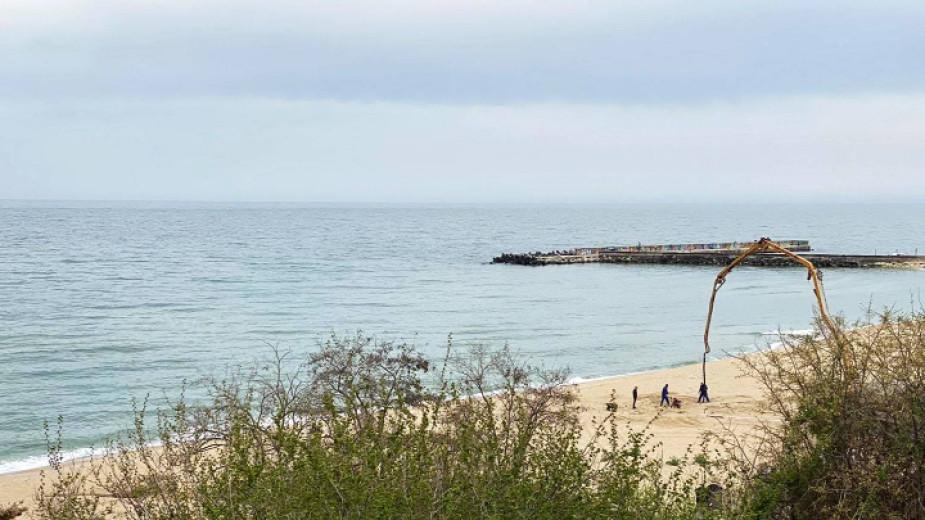 бетоновоз излива с помпа бетон на плажа